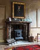 Gilt-framed, whimsical dog portrait above old log-burning stove in antique fireplace