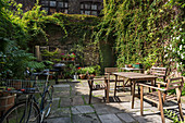 Table and chairs in planted courtyard of old English townhouse