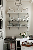 Crockery on shelves on wall above cooker and worksurface in corner of kitchen