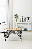 Delicate paper sculptures on white shelves behind designer table