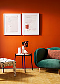Chair, round table and armchair with green velvet upholstery against orange wall with pictures