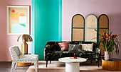 Chair, sofa, side tables and screen against pink and green wall in living room