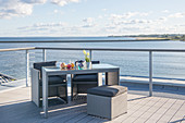 Grey outdoor furniture on open terrace with wooden deck and sea view