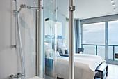 Schlafbereich mit Doppelbett, Terrassentür mit Meerblick und Bad Ensuite