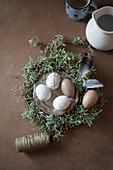 Besprenkelte Eier auf Zinnteller im Osternest mit Federn
