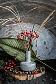 Still-life arrangement of rose hips and flowering Chinese reeds