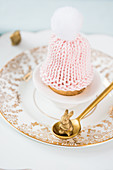 Knitted bobble-hat egg cosy on vintage-style plates