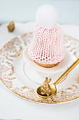 Gestrickte Mütze als Eierwärmer auf nostalgischem Teller