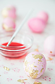 Pink eggs with gold leaf and bowl of dye