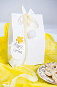 Easter bunny with lace ribbon on gift bag on yellow tissue paper