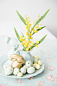 Mimosa flowers and oleander leaves in vase with Easter decorations