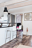 Bar stools at counter in white open-plan kitchen