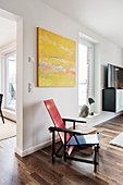Classic designer chair below yellow painting