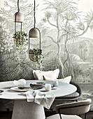 Round table with chairs above, pendant lights with house plants in front of wallpaper with jungle motif