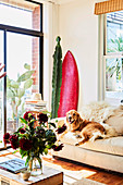Light upholstered sofa with dog, cactus and surfboard in the corner of the room, in the foreground a coffee table with a bouquet of flowers