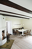 Open fireplace and wood-beamed ceiling in country-house-style dining room