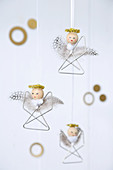 Small angel decorations made from paper clips, beads and feathers
