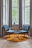 Blue armchairs and side table on round, mustard-yellow rug in window bay
