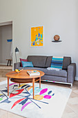 Round table on brightly patterned rug in front of grey sofa