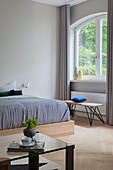 Doppelbett aus Holz und Bank unter Fenster in Altbauwohnung