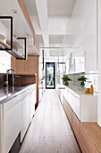 Narrow kitchen with glossy white fronts