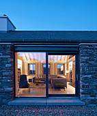 Blick durch Terrassentür ins beleuchtete Wohnzimmer