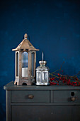 Lanterns and branch of red berries on top of chest of drawers