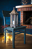 Lantern and branch of berries on wooden chair with fairy lights on floor