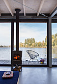 Modern houseboat: log-burner in front of glass wall