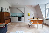 Simple fitted kitchen, dining area, sofa and bed in open-plan interior