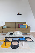 Coffee table with marble top on brightly patterned rug in front of sofa