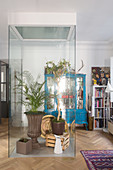 Houseplants in glass cubicle in living room of period apartment