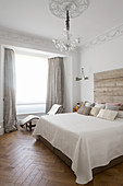 Double bed with rustic wooden headboard and lounger in bedroom