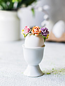 Easter egg with flower decoration in an eggcup
