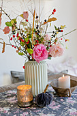 Autumn bouquet of roses, rose hips, astrantias and branches of sloes and spindle fruits