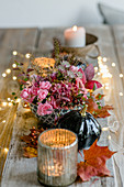 Arrangement of roses and candle lanterns on table