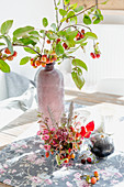 Autumn arrangement of crab apple branches, flowers and black pumpkin