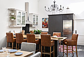 Dining table, leather chairs and black cabinets with integrated fridge in kitchen-dining room