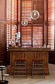 Bar stools at old wooden counter in bay window with shutters