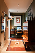 Desk against dark green wall in hall with veneered cabinet in foreground