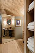 Mirrored door in bathroom with vaulted ceiling and wooden floor