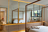 Mirrored, fitted cupboards and modern, wooden, four-poster bed in bedroom