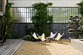 Group of designer Butterfly chairs and table in gravel courtyard