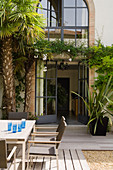 Exotic plants and seating area on terrace outside large arched French windows