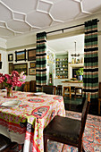 South African cotton print Obama table cloth in dining room with view through to kitchen and curtains
