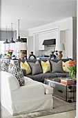 Scatter cushions on white and grey sofas and metal trunk used as coffee table in open-plan interior