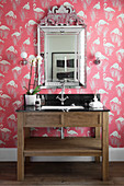 Washstand with marble top below silver-framed mirror on wall with flamingo-patterned wallpaper