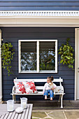 Little girl sits with dog on bench in front of blue and white wooden house