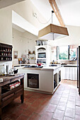 Country house kitchen with kitchen island and terracotta tiles