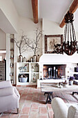 Living room with fireplace and wrought iron chandelier in country house